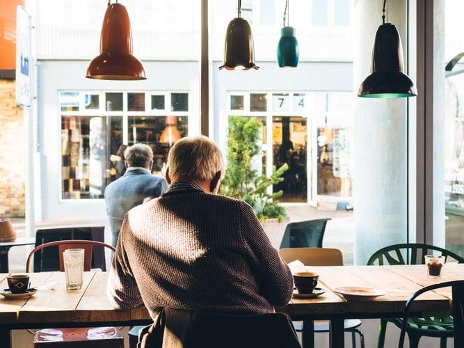 Older man sitting inside coffee shop.